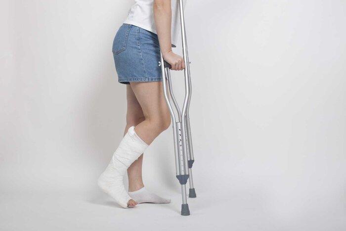 松葉杖で歩く女性