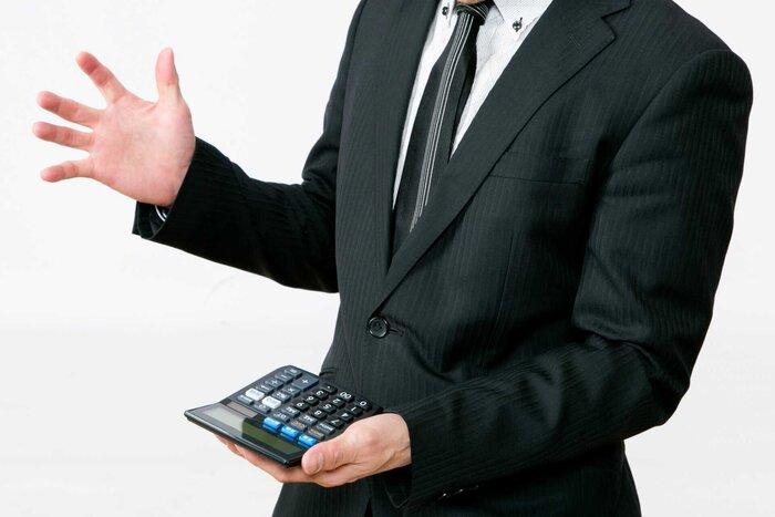 電卓をもったスーツ姿の男性