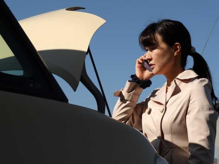 トランクの開いた車のそばで携帯電話をかけている女性